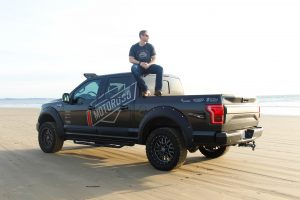 Founder of Motoroso sitting on the roof of his black pickup truck on the beach.