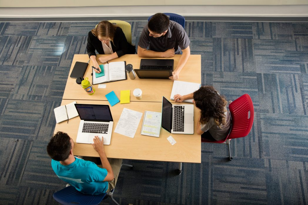Overhead shot of four students working at a table.